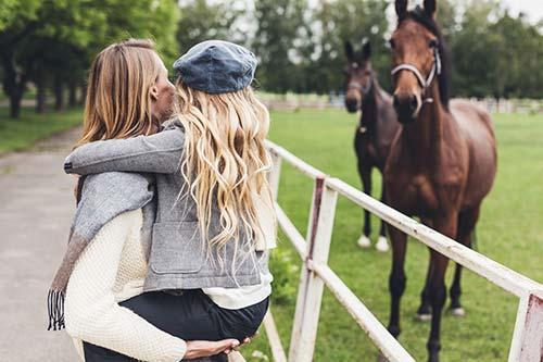 Mutter mit Kind auf dem Arm bei Pferden