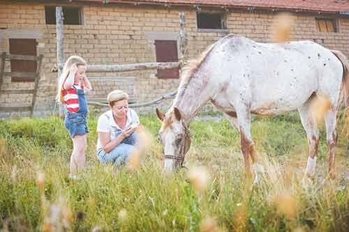 Mutter ohne Angst mit ihrer Tochter beim Pferd